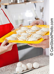 Chefs Holding Tray With Uncooked Pasta
