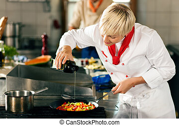 Chefs in a restaurant or hotel - Two chefs in teamwork - man...