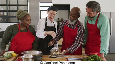 Front view of a multi-ethnic group of senior adults at a cookery class in a restaurant kitchen, the diverse group of adult students standing around a table preparing food and listening to instructions from a Caucasian female chef wearing chefs whites and a black hat and apron, rolling dough through ...