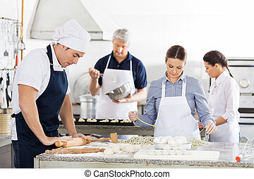 Chefs Making Pasta Together In Kitchen