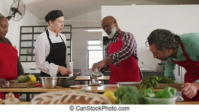 Side view of a multi-ethnic group of senior adults at a cookery class in a restaurant kitchen, the diverse group of adult students standing around a table preparing food and listening to instructions from a Caucasian female chef wearing chefs whites and a black hat and apron, rolling dough through a...