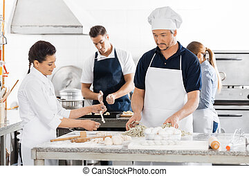 Chefs Preparing Pasta At Kitchen Counters