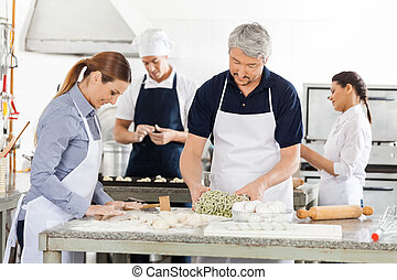 Chefs Preparing Pasta Together In Kitchen