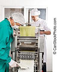Chefs Processing Ravioli Pasta In Machine