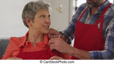 Front view of a senior Caucasian man helping a senior Caucasian woman to fasten her red apron, standing in cookery class, preparing before cooking, in slow motion