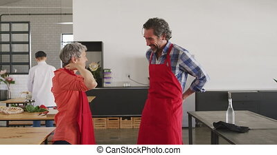 Side view of a Caucasian senior man and woman putting on their red aprons, standing and talking in a cookery class, a female Caucasian chef in chefs whites in the background, in slow motion