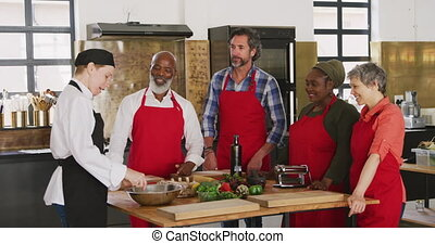 Front view of a multi-ethnic group of senior adults at a cookery class in a restaurant kitchen, the diverse group of adult students standing around a table of ingredients listening to instructions from a Caucasian female chef wearing chefs whites and a black hat and apron, in slow motion
