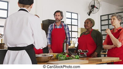 Front view of a multi-ethnic group of senior adults at a cookery class, the diverse adult students listening to instructions from a Caucasian female chef wearing chefs whites and a black hat with back to camera in the foreground, standing around a wooden table of ingredients in slow motion
