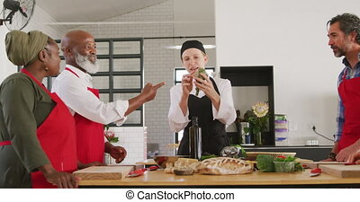 Front view of a multi-ethnic group of senior adults at a cookery class, the diverse adult students in discussion with a Caucasian female chef wearing chefs whites and a black hat and apron, standing around a wooden table of ingredients, in slow motion