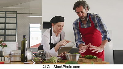 Front view of a senior Caucasian man at a cookery class, listening to instructions from a Caucasian female chef wearing chefs whites and a black hat and apron using a tablet computer, in slow motion