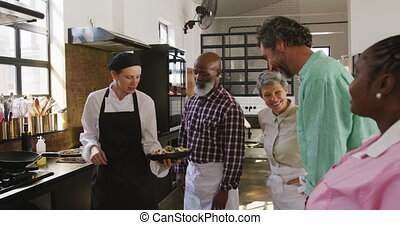 Front view of a multi-ethnic group of senior adults at a cookery class in a restaurant kitchen, the diverse group of adult students listening to instructions from a Caucasian female chef wearing chefs whites and a black hat and apron, in slow motion