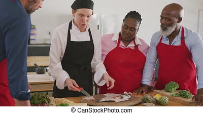 Front view close up of a multi-ethnic group of senior adults at a cookery class in a restaurant kitchen, standing around a wooden table listening to a Caucasian female chef wearing chefs whites explaining and showing them how to fillet a raw fish on a wooden cutting board, in slow motion