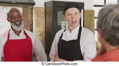 Over the shoulder view of a senior African American man and a senior Caucasian woman at a cookery class, the adult students listening to instructions from a Caucasian female chef wearing chefs whites and a black hat and apron, in slow motion