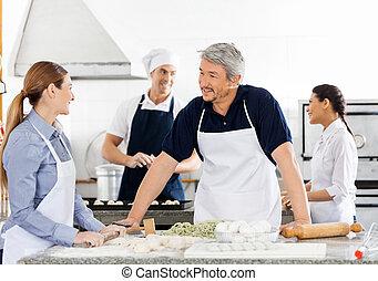 Chefs Talking While Preparing Pasta At Kitchen