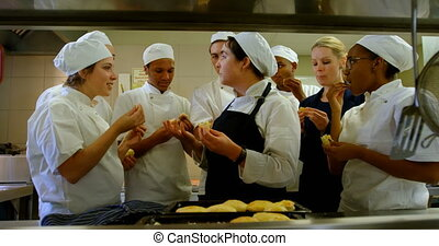 Chefs testing cookie in kitchen at restaurant 4k