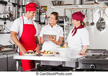 Chefs Using Tablet Computer At Kitchen Counter