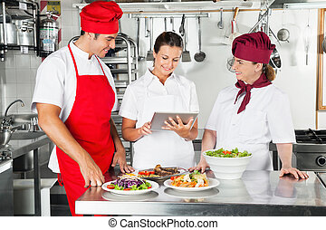 Chefs Using Tablet Computer In Kitchen