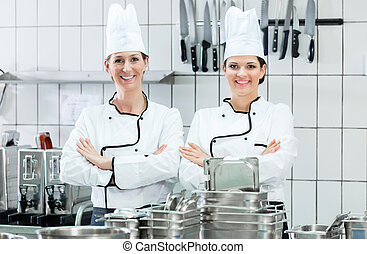 Chefs wearing working clothes in industrial kitchen