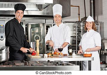 Chefs Working In Industrial Kitchen