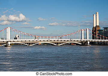 Chelsea Bridge over the river Thames against blue sky with white clouds and with Battersea Power station