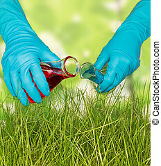 Chemical flask with experimental liquid against green grass
