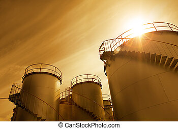 chemical plant's storage tanks at sunset hour