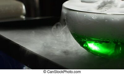 Chemical white smoke coming out of a glass flask with green liquid