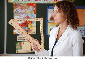 chemisier, debout, professeur, school., règle, blackboard., main, aside., sien, regarde, portrait, blanc, girl