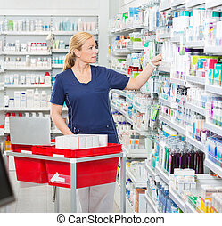 Chemist Arranging Medicines In Shelves At Pharmacy