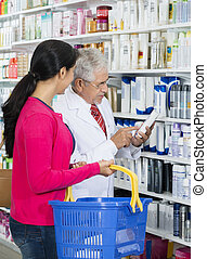 Chemist Assisting Female Customer In Buying Shampoo