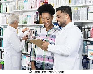 Chemist Explaining Prescription To Customer In Pharmacy