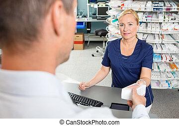 Chemist Giving Medicine Box To Male Customer In Pharmacy
