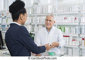 Chemist Giving Medicine To Female Customer