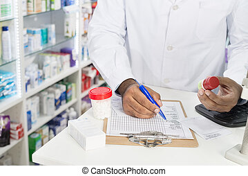 Chemist Holding Pill Bottle While Writing On Paper