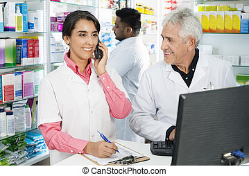 Chemist Looking At Female Colleague Using Telephone At Counter