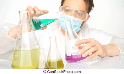 chemist mixing chemicals - man chemist mixing liquid...