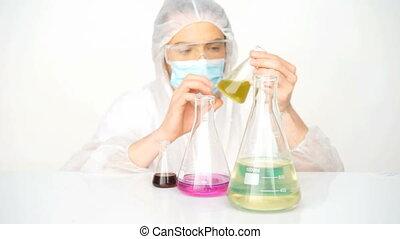 chemist mixing chemicals - man chemist mixing liquid...