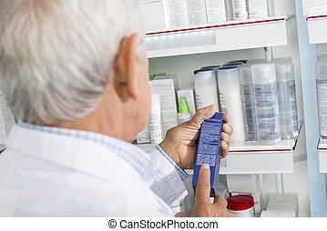 Chemist Reading Instructions On Medicine Box In Pharmacy