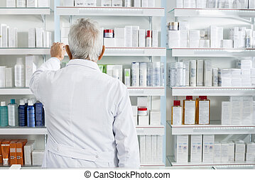 Chemist Searching Medicines In Shelves At Pharmacy