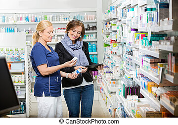 Chemist Showing Eye Drops To Customer Holding Digital Tablet