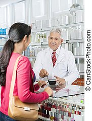 Chemist Swiping Card While Looking At Customer In Pharmacy