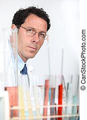 Chemist with rack of test tubes