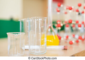 Chemistry glassware with liquid formula and molecular structure model at the science classroom laboratory desk.
