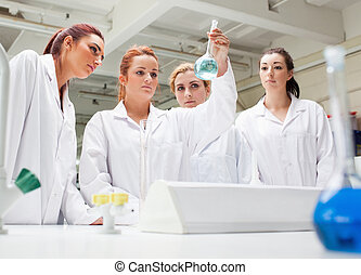 Chemistry students looking at a liquid