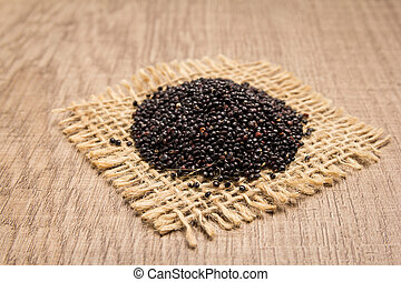 Black Quinoa seed. Grains on square cutout of jute. Wooden table. Selective focus.