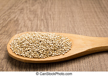Golden Quinoa seed. Grains in wooden spoon. Rustic.