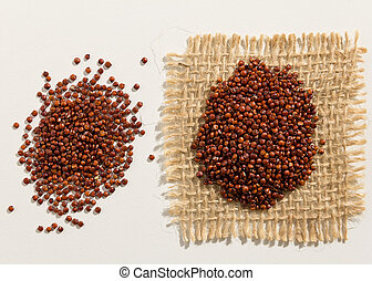 Red Quinoa seed. Close up of grains spreaded over white table.