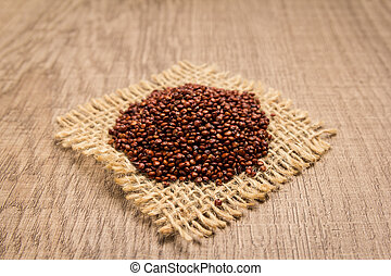 Red Quinoa seed. Grains on square cutout of jute. Wooden table. Selective focus.