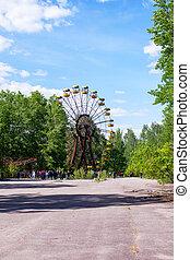 Chernobyl, Ukraine - June 01, 2021: Tourists near the abandoned ferris wheel