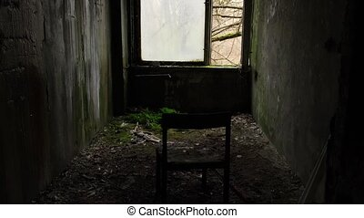 Chernobyl zone, Ukraine. 4K. Visit to Pripyat Ghost Town. View of the window and back of a chair from inside an abandoned room in house 2020
